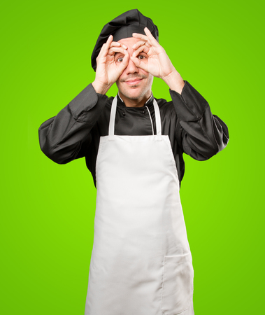 Surprised young chef doing an observe gesture