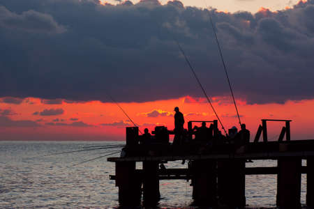 Fishermans on a pier in the evening on a sea photo