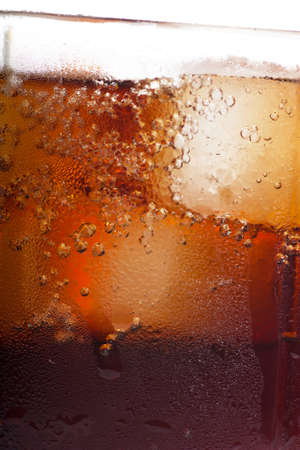 Cold cola in a glass with ice cubes photo