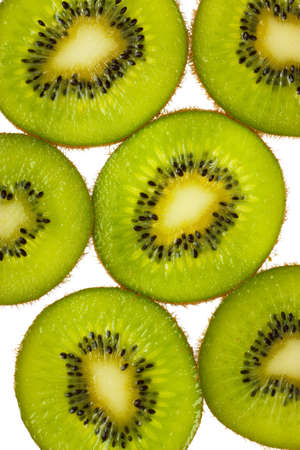 Close-up view of kiwi slices over white background photo