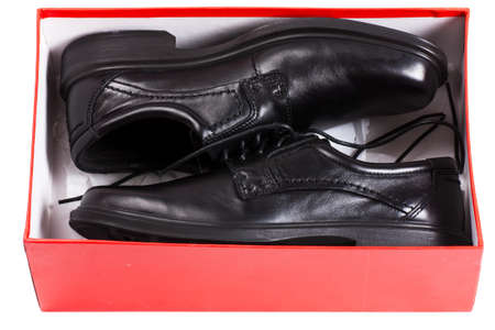 A pair of black men shoes in a red box isolated over white background photo