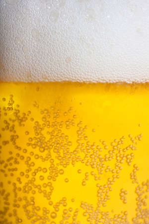 beer background: Orange beer and white froth background. Closeup view.
