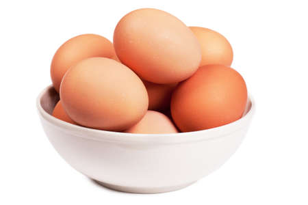 Brown eggs in a bowl over white background photo