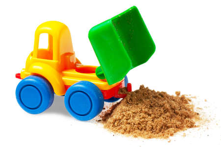 Colorful toy truck with sand over white background photo