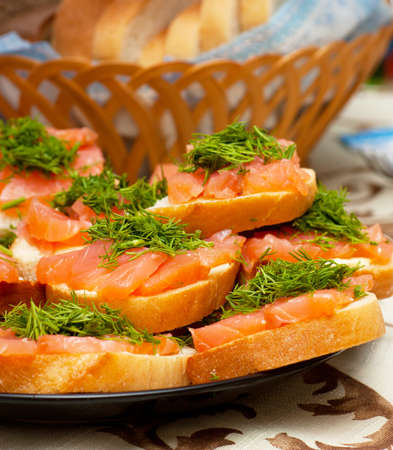 A heap of sandwiches with red fish meat and green parsley photo