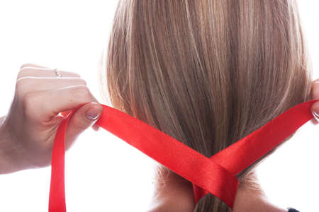 Young woman braids her hair with red ribbon photo