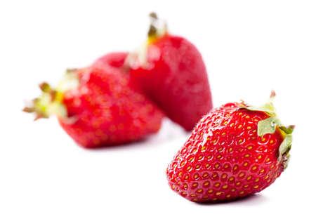 Closeup view of fresh strawberries over white background photo