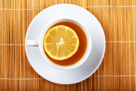 Top view of white cup of green tea with lemon on a white plate Stock Photo - 13718511