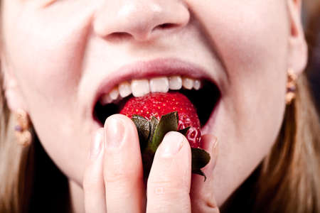 Young woman eating fresh juicy strawberry photo