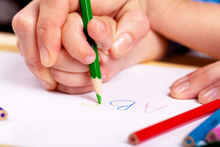 Child hand with pencil and woman hand helping to write letters photo