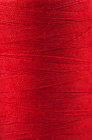 Macro view of red thread wound on a spool photo
