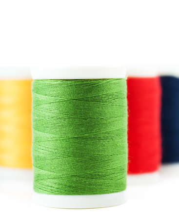 Four thread spools over white background