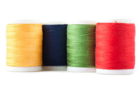 Four spools with green, yellow, blue and red threads