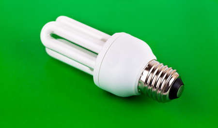 Energy saver bulb over green background photo