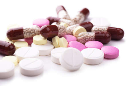 Macro view of heap of pills and capsules over white background Stock Photo