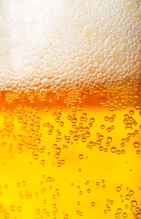 Orange beer and white froth background  Closeup view
