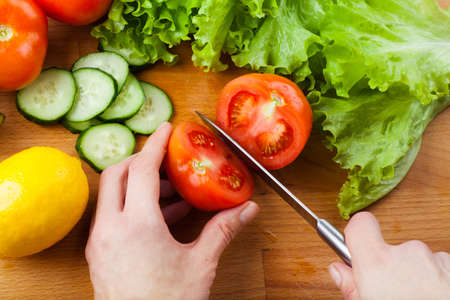 Woman cutting vegetables  tomato, cucumber, salad  on a wooden table