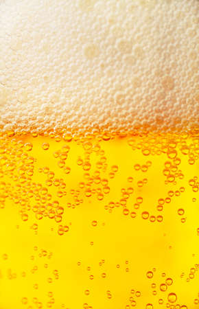 Orange beer and white froth background  Closeup view  photo
