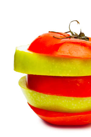 multi layered: Sections of fresh ripe green apple and red tomato isolated over white background  Diet concept