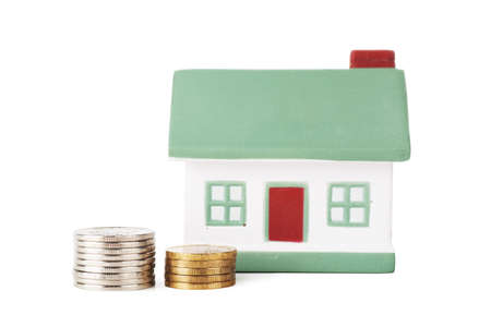 Little house toy and two stacks of coins isolated over white background Stock Photo - 17612728