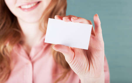 Image of smiling business woman holding her visiting card Standard-Bild