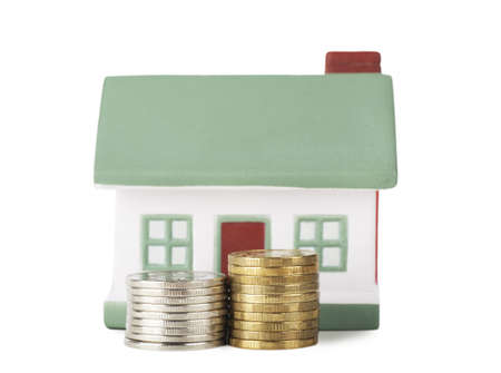 Little house toy and two stacks of coins isolated over white background Stock Photo - 17741317