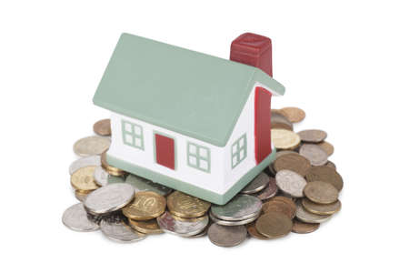 Little house toy on a heap of coins isolated over white background Stock Photo - 17741321