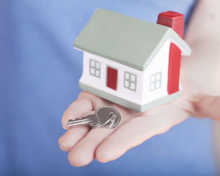 Little house toy and key in womans hand photo