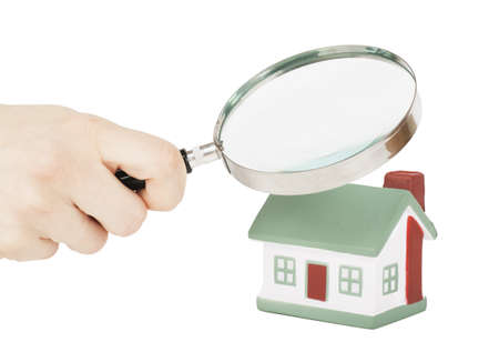 Toy of house and hand with magnifying glass isolated over white background Stock Photo - 17741316