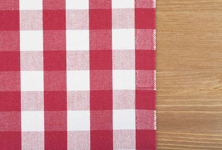 Checked with red and white tablecloth on a wooden table photo
