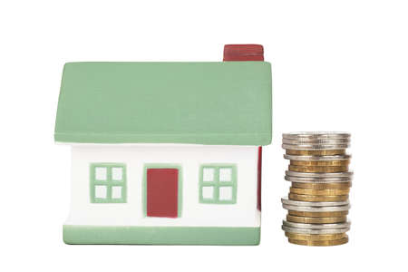 Little house toy and stack of coins isolated over white background Stock Photo - 17899018
