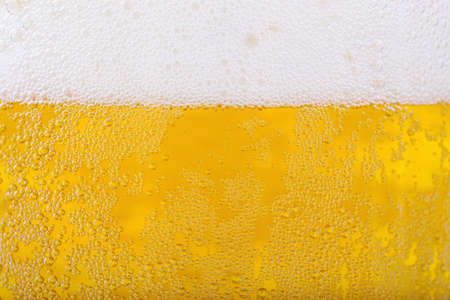 Beer and white froth background. Closeup view.