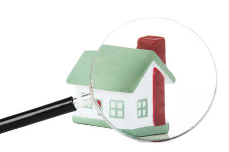 Toy of house and hand with magnifying glass isolated over white background Stock Photo - 17899044