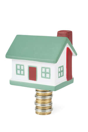 Little house toy on a stack of coins isolated over white background Stock Photo - 17899045