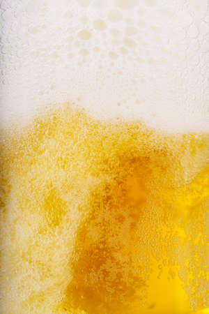 Beer and white froth background. Closeup view. photo