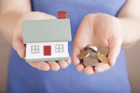 Little house toy and money in woman's hands Stock Photo - 18090738