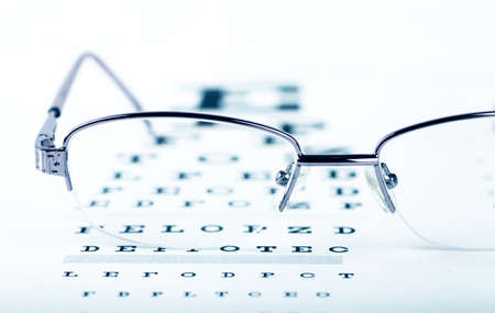 Closeup view of eyeglasses on a eye chart photo
