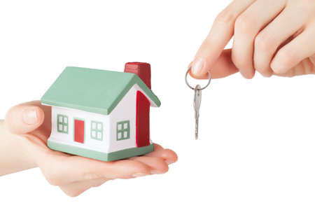 Little house toy and key in hands isolated over white background photo