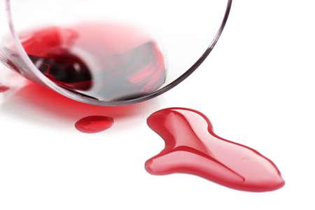 Vin rouge renversé de verre sur fond blanc