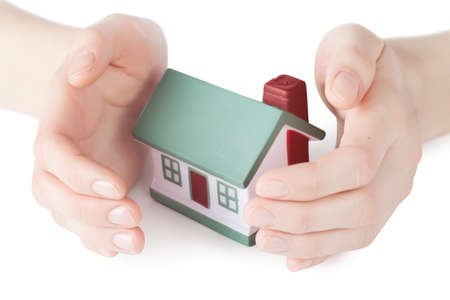 Little house toy covered by hands isolated over white background Stock Photo - 18524112