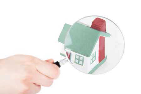 Toy of house and hand with magnifying glass isolated over white background Stock Photo - 18995535