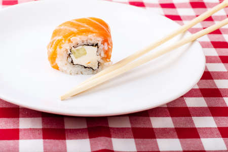 Sushi, soy and ginger with chopsticks on a white plate photo