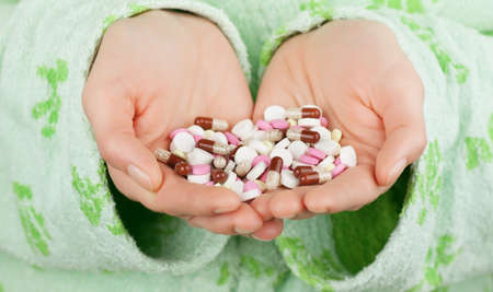 Closeup view of many pills in cupped hands photo