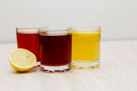 drinks of different colors and texture in glass cups on table on white background. A place for a label. Copyspace