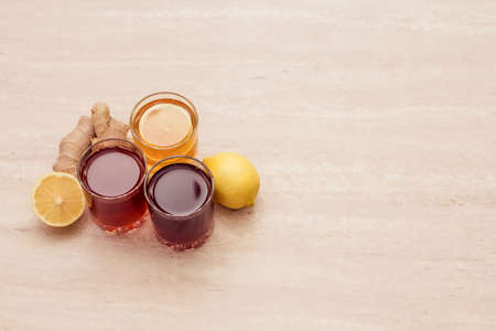 drinks of different colours and textures in glass cups on table on  light background. A place for a label. Copyspace