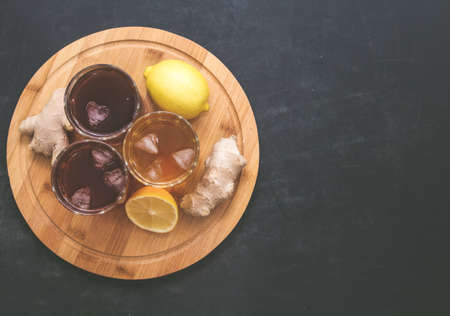 Kombucha. drinks of different colours and textures in glass cups on table on black background. A place for a label. Copyspace