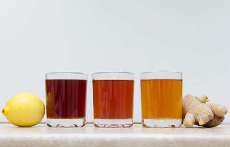 drinks of different colors and texture in glass cups on table on white background.KOMBUCHA BLUEBERRY APRICOT UNFLAVORED.