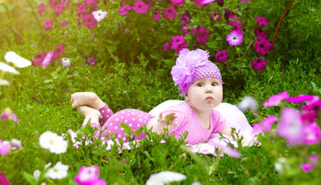 The baby lies on the grass in flowers