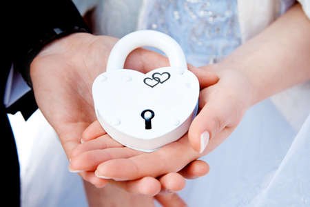 Hands and white lock. Wedding ceremony.   The bride and groom loving couple bonded along their Union. The symbol and concept of eternity, love, beginning, new and old.