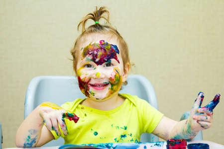 Beautiful little girl drawing in the album, Smeared face and hands paint, eyes. Stock Photo